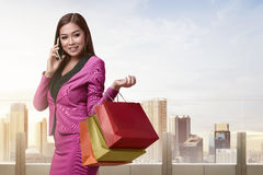 Young asian business woman with shopping bags on the phone Royalty Free Stock Photography