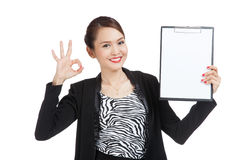 Young Asian business woman show OK and blank clipboard Stock Images