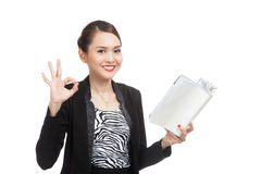 Young Asian business woman show OK with a book Royalty Free Stock Photography