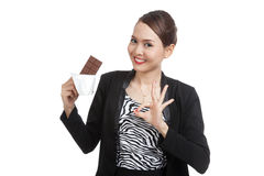 Young Asian business woman show OK with chocolate bar Stock Images