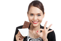 Young Asian business woman show OK with chocolate bar Royalty Free Stock Photography