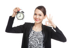 Young Asian business woman show OK with a clock Stock Images