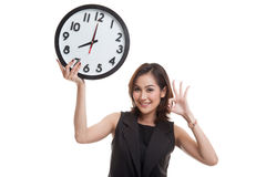 Young Asian business woman show OK with a clock. Royalty Free Stock Image