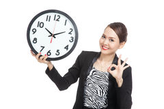 Young Asian business woman show OK with a clock Stock Photos