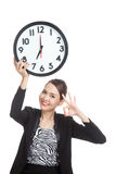 Young Asian business woman show OK with a clock Royalty Free Stock Photography