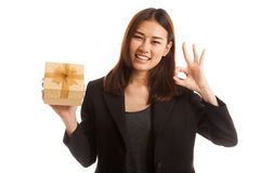 Young Asian business woman show OK with a gift box. Young Asian business woman show OK with a gift box  isolated on white background Stock Photography