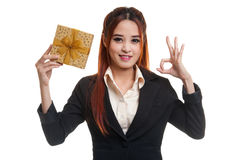 Young Asian business woman show OK with a gift box. Young Asian business woman show OK with a gift box  isolated on white background Royalty Free Stock Image