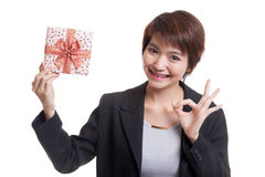 Young Asian business woman show OK with a gift box. Royalty Free Stock Photos