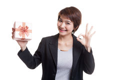 Young Asian business woman show OK with a gift box. Stock Photography