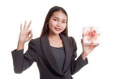 Young Asian business woman show OK with a gift box. Young Asian business woman show OK with a gift box  isolated on white background Stock Images