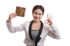 Young Asian business woman show OK with a gift box. Young Asian business woman show OK with a gift box  isolated on white background Royalty Free Stock Photos