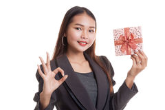 Young Asian business woman show OK with a gift box. Young Asian business woman show OK with a gift box  isolated on white background Royalty Free Stock Photography