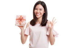 Young Asian business woman show OK with a gift box. Young Asian business woman show OK with a gift box  isolated on white background Stock Photo