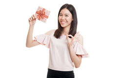 Young Asian business woman show OK with a gift box. Young Asian business woman show OK with a gift box  isolated on white background Royalty Free Stock Photo