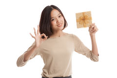 Young Asian business woman show OK with a gift box. On white background Stock Photography
