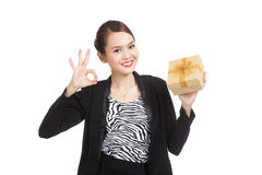 Young Asian business woman show OK with a golden gift box. Isolated on white background Royalty Free Stock Photography
