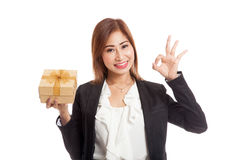 Young Asian business woman show OK with a golden gift box. Isolated on white background Stock Images