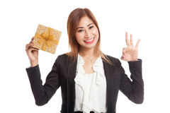 Young Asian business woman show OK with a golden gift box. Isolated on white background Royalty Free Stock Images