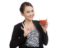 Young Asian business woman show OK with tomato juice Stock Photography