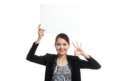 Young Asian business woman show OK with  white blank sign Royalty Free Stock Image