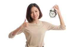 Young Asian business woman show thumbs up with a clock Royalty Free Stock Photography