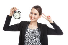 Young Asian business woman show victory sign with a clock Royalty Free Stock Photos