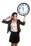 Young Asian business woman show victory sign with a clock. Stock Image