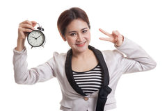 Young Asian business woman show victory sign with a clock. Stock Images