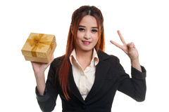 Young Asian business woman show Victory sign with a gift box. Young Asian business woman show Victory sign with a gift box isolated on white background Royalty Free Stock Image