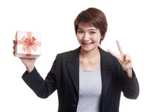 Young Asian business woman show Victory sign with a gift box. Royalty Free Stock Image