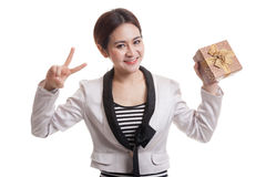Young Asian business woman show Victory sign with a gift box. Young Asian business woman show Victory sign with a gift box isolated on white background Royalty Free Stock Images