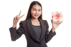 Young Asian business woman show Victory sign with a gift box. Young Asian business woman show Victory sign with a gift box isolated on white background Stock Photography