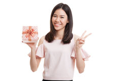 Young Asian business woman show Victory sign with a gift box. Young Asian business woman show Victory sign with a gift box isolated on white background Royalty Free Stock Photography
