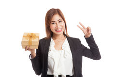 Young Asian business woman show Victory sign with a golden gift Royalty Free Stock Photo