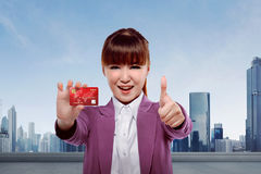 Young asian business woman showing credit card. Against cityscape background Stock Photography