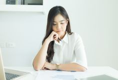 Young asian business woman smiling and thinking idea about work at her desk in modern office. stock photography