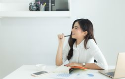 Young asian business woman smiling and thinking idea about work at her workplace stock photography