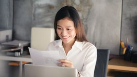 Young asian business woman smiling at workplace and reading paper in office stock photo