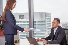 Young Asian business woman in suit brought report to her boss royalty free stock images