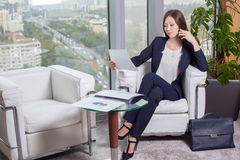 Young asian business woman in suit looking at the chart on the sheet Stock Photos