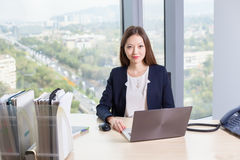 Young asian business woman in suit working on laptop Stock Photos