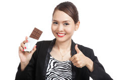 Young Asian business woman  thumbs up with chocolate bar Royalty Free Stock Images
