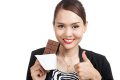 Young Asian business woman thumbs up with chocolate bar Royalty Free Stock Photos