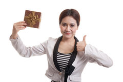 Young Asian business woman thumbs up with a gift box. Stock Photo