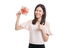 Young Asian business woman thumbs up with a gift box. Stock Image