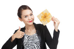 Young Asian business woman thumbs up with a golden gift box. Isolated on white background Royalty Free Stock Photography