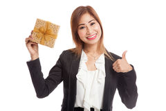 Young Asian business woman thumbs up with a golden gift box Royalty Free Stock Image