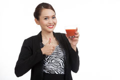 Young Asian business woman thumbs up with tomato juice Royalty Free Stock Images