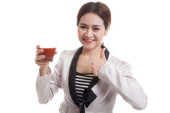 Young Asian business woman thumbs up with tomato juice. Stock Photo