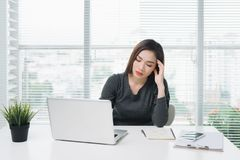 Young asian business woman with tired eyes and headache.  royalty free stock photo
